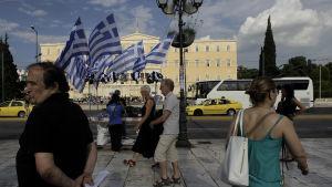 Greker promenerar utanför parlamentet i Aten.