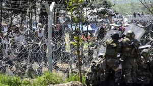Makedonska gränspoliser och migranter vid gränsstängslet på söndagen 10.4.2016