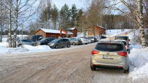Bilar står parkerade längs snöig sandväg