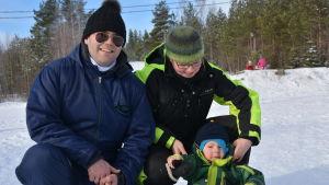 Fredrik, Åsa och Evert Teir framför pulkabacken vid Öjberget. Fredrik har solglasögon på sig.
