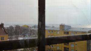 Foto taget från fastigheten Mau-Mau i Hangö. På bilden syns spaet på Fabriksudden och ett stort gult flervåningshus. I bakgrunden skymtar det öppna havet.