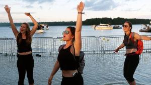 Tre kvinnliga besökare av Weekend-festivalen i Helsingfors sträcker upp sina händer i luften samtidigt som de dansar nära strandkanten. Bakom syns havet och båtar som lagt till invid festivalområdet.
