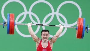 Nordkoreansk tyngdlyftare håller vikterna högt i luften.