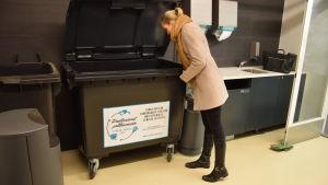 Alexandra Peth tittar efter om det redan finns skinkfett i sopkärlet.