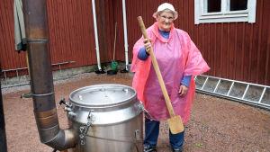 En kvinna iklädd rosa regnrock håller i en stor slev vid ett fältkök i rostfritt stål.