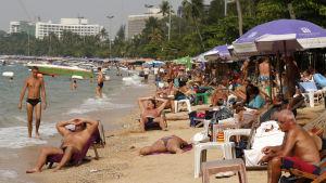 Turister på stranden i Pattaya i Thailand.