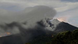 Ett tre kilometer högt och gråsvart askmoln stiger från vulkanen Turrialba i Costa Rica och rör sig mot huvuddstaden San José vars ljus syns i bakgrunden.