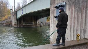 En fiskare vid Strömma kanal håller i ett metspö.