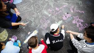 Frivilliga från Röda korset leker med barn på flyktinganläggningen i Rödbergen i Helsingfors.