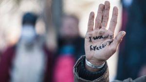 """En man som försökt korsa gränsen mellan Grekland och Makedonien sträcker fram sin hand med texten """"Jag vill ha frihet""""."""