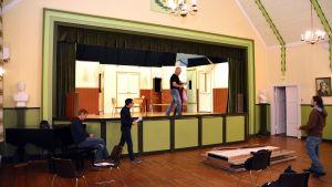 Skådespelare står på en scen och repeterar