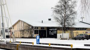 En gul gammal magasinbyggnad i Ekenäs norra hamn. På ena sidan syns en björk. Marken är täckt av snö.