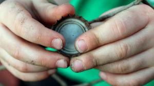 Jordiga barnhänder med sorgkanter under naglarna håller i ölkork.