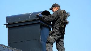Sotare förbereder sotning av skorsten genom att skjuta undan skyddstak av plåt.