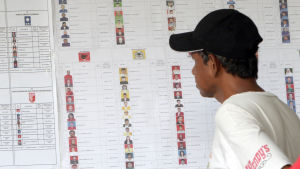 En väljare studerar en kanidatlista i Jakarta