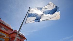 Solen skiner genom Finlands flagga som vajar på motorbåt.
