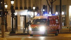 En polis står bakom en ambulans på en i övrigt folktom gata i Paris.