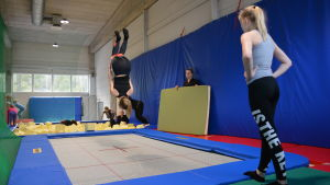 Flicka gör volt på trampolin under gymnastiklektion.