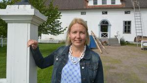 Vik. museiamanuens Johanna Enroth framför Kuddnäs huvudbyggnad.