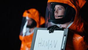 """Lingvisten Louise (Amy Adams) är iklädd full skyddsutrustning och håller upp en tavla där hon skrivit """"human"""" / människa och försöker förklara vem hon är för utomjordingarna."""