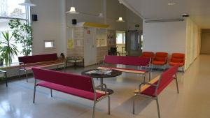 Bänkar och bord i väntrummet i Pojo hälsostation.