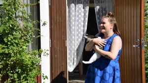 En kvinna i blå klänning står med en katt i famnen. I bakgrunden skymtar en ingång till ett hus.