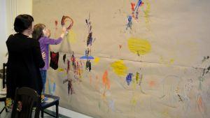 Barn ritar på väggen.