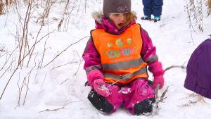 Femåriga Taru Kantola leker i snön.