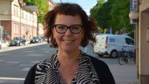 Kvinna med rödbrunt hår och glasögon står leende på Trädgårdsgatan i Åbo.
