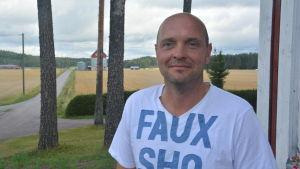 Tom Kvarnström med sädesfält i bakgrunden.