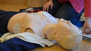Kvinna visar hur en defibrillator fungerar.