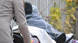 Kvinna skjuter på rullstol där det sitter en äldre person.
