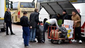 Många personer lastar på en buss
