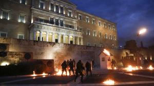 Demonstranter kastar brandbomber mot polisen utanför det grekiska parlamentet.