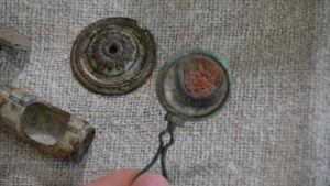 På bilden används ett gammalt förstoringsglas hittat i åkern för att förstora en läppstiftsburk. Bredvid ligger ett mantelspänne och en del av en tvärflöjt.