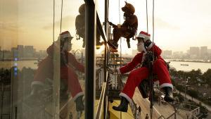 Fönstertvättare i julkostymer i Japans huvudstad Tokyo på julafton.