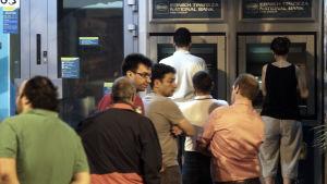 Folk köar till bankautomater i Aten den 27 juni 2015.