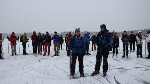 En instruktör och en långfärdsskrinnare står framför en grupp långfärdsskridskoåkare på isen.
