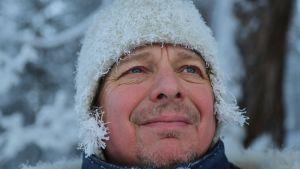 Miehen kasvot lumisessa maisemassa. Pipon alta pilkistävät hiukset ovat valkeassa kuurassa ja myös pipoa peittää hentoinen kuura.