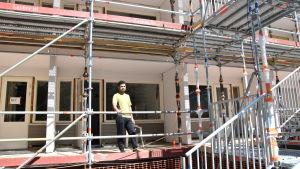 Omar Al-Saffar bor mitt bland byggställningarna.