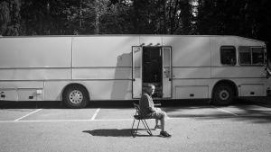 Mies istuu parkkipaikalla bussin vieressä.