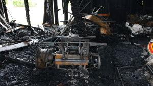 Resterna av den uppbrända fyrhjulingen. Runt omkring den ligger aska och förkolnade plankor.