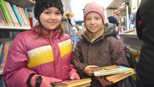 Cecilia Andersson och Vilma Nikkanen lånar böcker i Sibbos bokbuss.