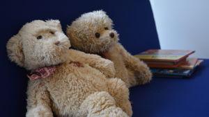 Två teddybjörnar och en hög med böcker på en soffa.