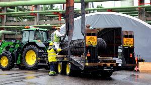 arbetande män vid traktor och släpvagn