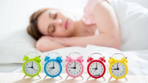 En kvinna som sover och har många väckarklockor bredvid sängen.