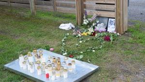 Blommor och ljus utanför bostaden till den unga flickan som blev mördad i Ekenäs.