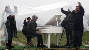 Ai Weiwei tog med sig ett piano till ett flyktingläger på gränsen mellan Makedonien och Grekland.