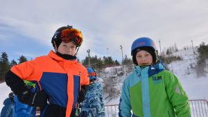 Jesse Backholm står till vänster, han har stora skidglasögon över pannan och en orange och blå jacka. Till höger som Jeri Kuoppala med en grön och blå jacka och en blå hjälm på huvudet. De står i liftkön till Öjberget.