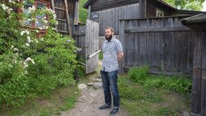 John Björkman står på bakgråden vid ett hus på Klosterbacken.